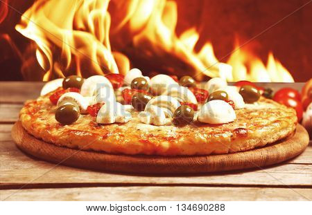 Tasty hot pizza with mushrooms on wooden table against fire flame background
