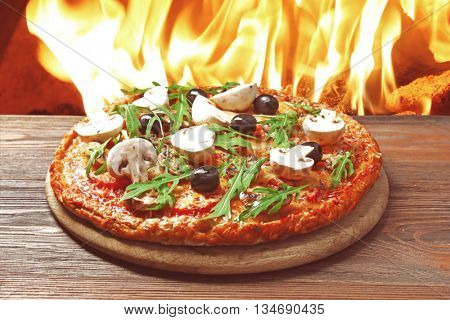 Tasty pizza with vegetables and arugula on wooden table against fire flame background