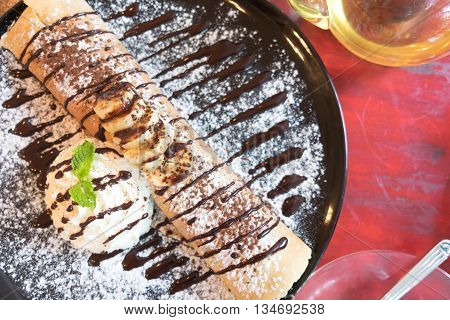 delicious pancake with chocolate syrup and ice cream