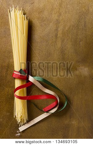 Pasta spaghetti Italian flag colors ribbons tied on a wooden table