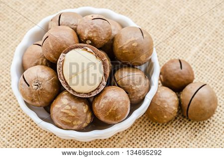 macadamia nuts in white bowl on sack background.