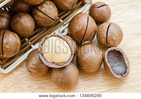 The Macadamia nut in weave basket on wooden background