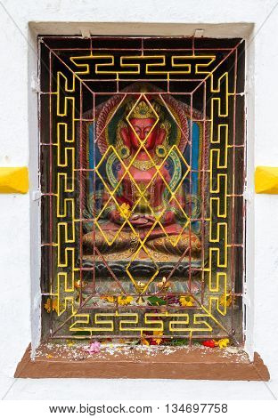 Nepalese sculpture of Buddha in a closed door with the lit oil lamps and worshiped flowers.