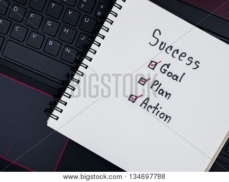 Handwriting word Success Goal Plan Action on blank notebook with laptop keyboard background