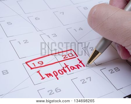 Woman hold a pen on right hand and write word important on calendar desk with red ink 1