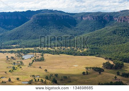 Aerial mountain valley landscape. Australian outback nature with eucalyptus covered mountains and deforested valley