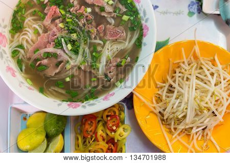 Traditional Vietnamese pho noodle soup with rare beef, tendon and tripe served with onions and cilantro.