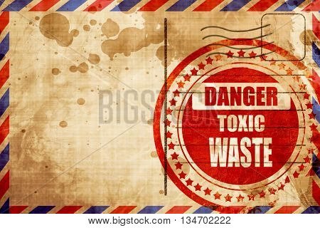 Toxic waste sign, red grunge stamp on an airmail background