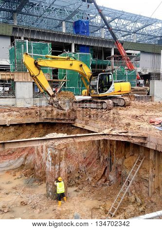 JOHOR, MALAYSIA -JANUARY 19, 2016: Excavators machine is heavy construction machine used to do soil excavation work at the construction. Powered by long hydraulic arm with bucket.