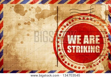 we are striking, red grunge stamp on an airmail background