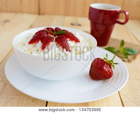Homemade cottage cheese with fresh strawberries mint leaves decoration in a white bowl and a cup of coffee. Useful eco breakfast. Healthy eating.