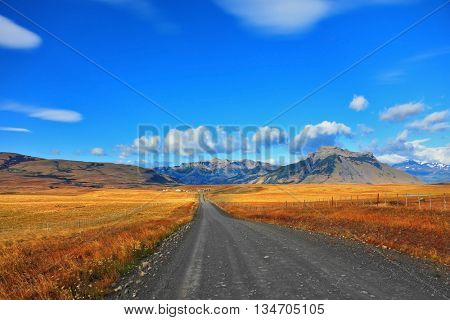 Steppes of Patagonia. Dirt road passes between the plains to the distant mountains