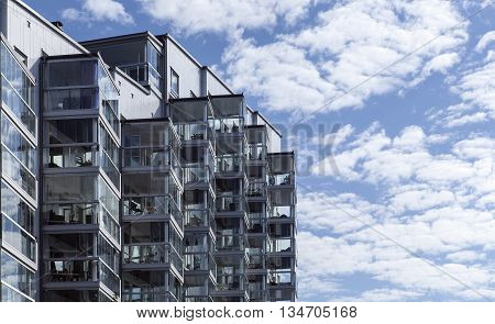 Closeup view of a modern façade. Balconies, glasses and windows on the new modern façade I morning lit. Clouds and a blue sky.