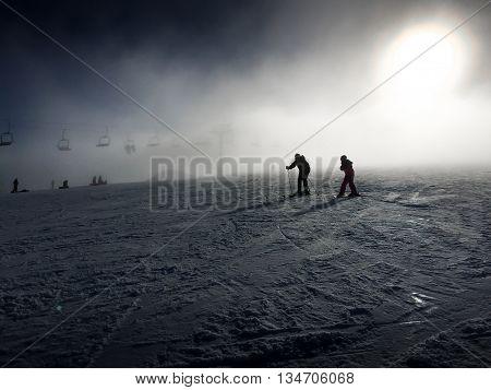 A couple skiing on a dark hazy day