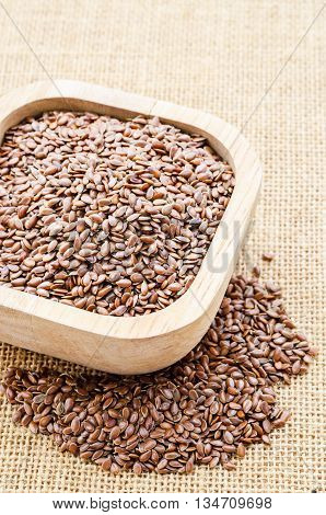 Heap of brown linseed in wooden cup on sack background concept for healthy nutrition