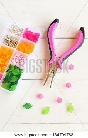 Supplies and tool for creating handmade jewelry. Plastic box with assorted beads, flowers, leaves and metal rings and pins. Pliers. Close-up. Vertical photo