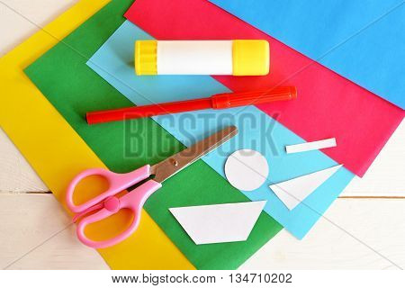 Glue stick, colored sheets, scissors, red marker, paper patterns. Supplies set to create fun summer card. Patterns for crafts. Stationery. Baby and preschool art lesson. Wooden background. Closeup