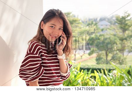 younger asian woman talking on smart phone with happiness emtion
