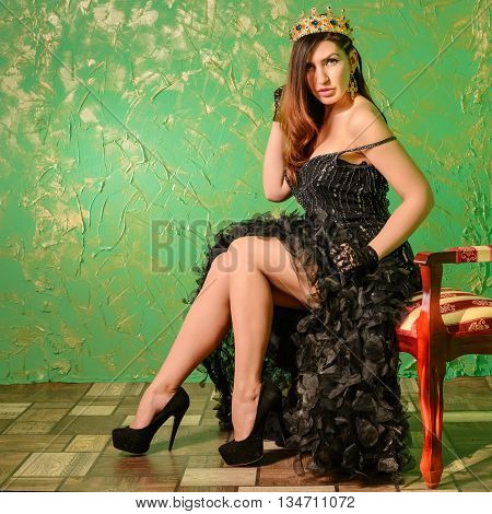 Girl in a black evening dress and a crown on his head is sitting on a banquette in a room with walls of Venetian plaster green.