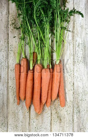 high-angle shot of some raw carrots with their leaves on a rustic white table