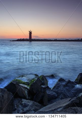 Beautiful seascape with lighthouse at the sunrise,sae breakwater .