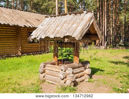 The old log cabin is well on the lawn in a pine forest