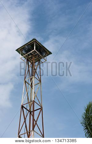 Loudspeakers broadcast tower with a blue sky background
