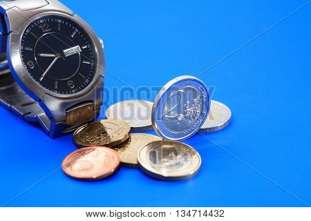 Set of European coins near wristwatch on blue background