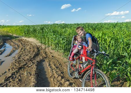 Teenage and preschooler siblings are cycling together on summer dirt road in green farm corn field