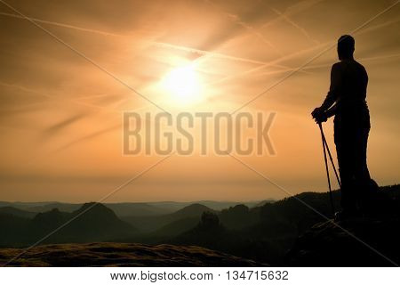 Silhouette Of Tourist With Poles In Hand. Sunny Spring Daybreak