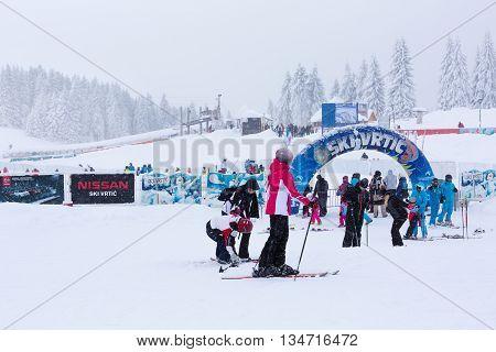 Kopaonik, Serbia - January 18, 2016: Panorama of ski resort Kopaonik during snowfall, people, skiers, snowy trees at winter time