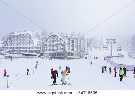 Kopaonik, Serbia - January 18, 2016: Panorama of ski resort Kopaonik during snowfall, people, skiers near ski lift ,snowy trees at winter time