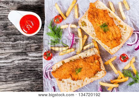 sandwich with ciabatta and Bread Crumb Coated fried pork chop with french fries red onion cherry tomatoes and dill on a parchment paper studio lights view from above