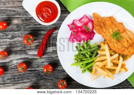 Bread Crumb Coated fried pork chop with french fries fried green bean and salad with dill and cabbage marinated in red wine vinegar and beet juice studio lights close-up view from above