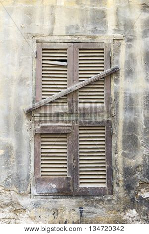 Old wooden window sealed with wooden planks.