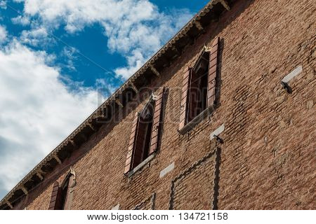 Ancient Facade with Visible Brick Work along Typical Water Canal in Venice Italy