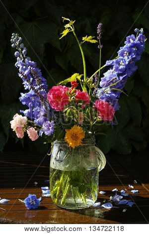 Sun after rain - colorful flowers bouquet in the garden with roses lavender grape leaves and blue delphinium