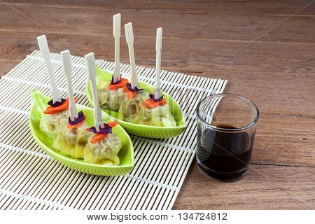Chinese steamed meat dumpling with sauce on green ceramic dish and on a garnished plate sitting on a wooden table