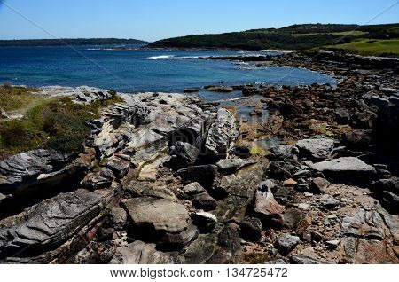 Close-up of sea surf. Shore with sea water and  rocks. Rocky coastline with sea water and boulders.