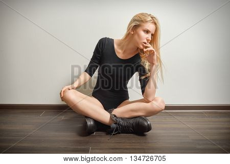 blond girl in black bodysuit and male boots sitting on floor