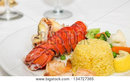 A lobster tail with shell shrimp rice and vegetables