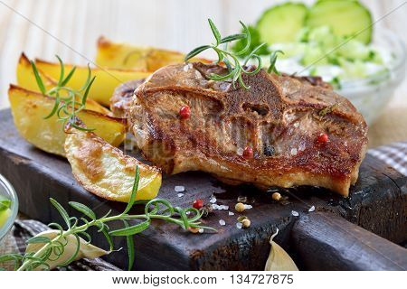 Greek meal: Fried lamb chops with baked potato wedges and tzatziki