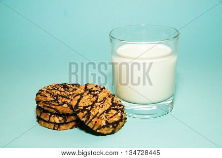 A glass of milk and cookies on blue