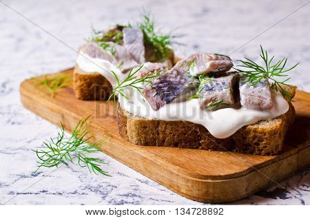 Sandwich with pieces of marinated herring with cream and dill. Selective focus.