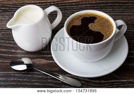 Cup Of Hot Coffee And Jug Milk On Dark Table