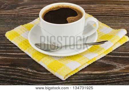 Hot Coffee And Spoon On Yellow Napkin On Dark Table