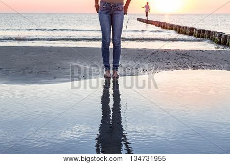 the legs of a woman reflected in the ocean at sunset