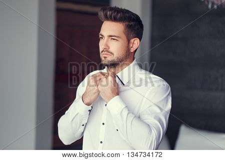 Young caucasian man dressing put on shirt indoor