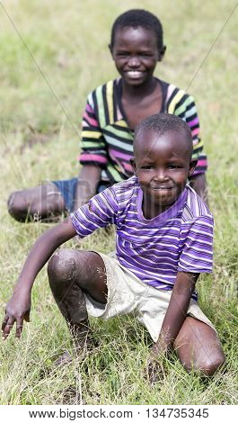 AFRICA, KENYA, MAY, 05, 2016 - Smiling African children sitting in the grass at Masai Mara National Park, Kenya, Africa