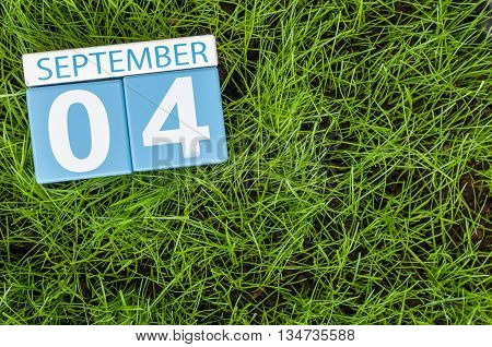 September 4th. Image of september 4 wooden color calendar on green grass lawn background. Autumn day. Empty space for text.
